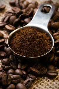 Coffee beans and ground coffee in a measuring spoon.