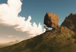 man pushing a boulder up a hill